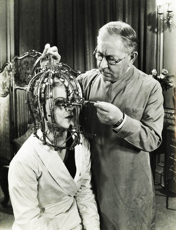 "Max Factor and his ""scientific device"", the Beauty Micrometer which detects defects in feminine beauty that are imperceptible to the naked eye. 1934."
