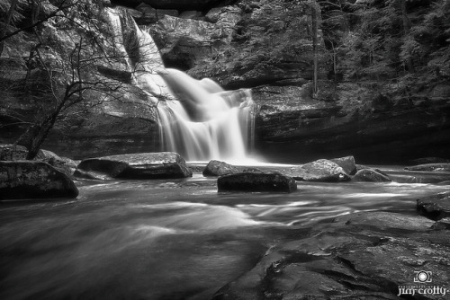 March at Cedar Falls Black and White Landscape Photography by Jim Crotty on Flickr.Via Flickr: Late winter at Cedar Falls in Hocking Hills State Park. A mid-winter thaw in late February provides a welcome preview of the warmth to come. The song of a thousand drips amongst the sandstone recesses welcomes you as you descends into the cool depths. The ice monoliths of January are reduced to size before winter makes a final appearance and a new layer of ice and snow takes hold, but only briefly. A heavy mist rises from the melting ice. On the trail are layers of ice, mud and sand, pounded into a solid, slippery covering by the passing of a thousand hiking boots. In the twilight of a winter evening the twisting roads through Hocking Hills go quiet with only the occasional traveler or local resident making their way home. Darkness falls just a few minutes later than the night before as the slow and steady progress toward spring begins. But winter doesn't give up easily. Inevitably there is one more snowstorm that blankets the trees in a coat of white, just when hopes are rising for an end to the long season of dormant slumber in the hills.