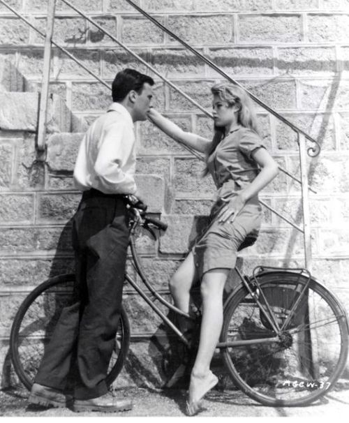 Brigitte Bardot rides a bike. Jean-Louis Trintignant invites her for Thanksgiving.