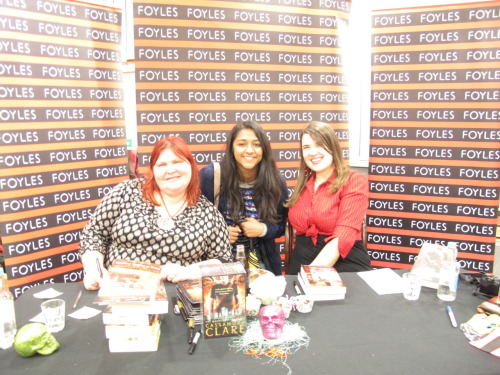 That's me with Cassandra Clare on the left and Sarah Rees Brennan on the right. As you can see i'm extremely happy to be meeting my favourite author! Ahhh! It's been almost a month since I went to an event held at Foyles in London for Cassandra Clare and I've been meaning to post about this but I guess I was a little lazy. This post is just as much for Radiya as it is for the followers because she's been nagging me to post about this since the event.  I was lucky enough to get a ticket last minute from a fellow blogger on twitter the night before the event :D So when I found my way to Foyles which proved more difficult than I expected we all patiently queued up and then waited upstairs in the special events room. Cassandra and Sarah came in, we all started cheering and clapped. Cassandra did a little quiz about the books and gave away some goodies as prizes. Unfortunately I didn't win anything :( Then came a q&a about TMI and ID. Sarah professed her great love for Sebastian which was adorable. Nobody could remember Simon's cat's name LOL (we had to name all 3 cats from TMI I could only remember Chairman Meow and Church but the 3rd was lost on me. I kept thinking Crookshanks lol)  When the event was finally over people who had picked up halloween masks with a sticker inside got a special goodie bag. I had a mask with a green sticker inside so I got my goodie bag filled with advanced reader copies of a few books, bookmarks, posters, badges, stickers, sweeties etc. It was all very exciting and I met a bunch of people whilst in the queue to meet Cassandra and Sarah and get my books signed. They all happened to be bloggers too which was amazing and they all knew each other from previous book events. They were really friendly and welcoming and told me loads of stories about blogger events and signings. Sarah and Cassandra were both amazing and extremely friendly. If they hadn't started talking to me I would have just stood there dumbfounded.  Here's a picture of one of the books Sarah signed for me. She said she was going to tell me what happens in City of Lost Souls to annoy Cassandra. Here's what she wrote instead…  I have to admit when I got home I did laugh. Finally here's Clockwork Angel signed by Cassandra and a special booklet called Magnus' vow (which i have not read yet :/)   Now I've come to the end of this post. I hope it wasn't terribly long and you enjoyed what I wrote especially you Radiya!
