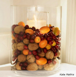 Pillar candle surrounded by walnuts, cranberries and kumquats
