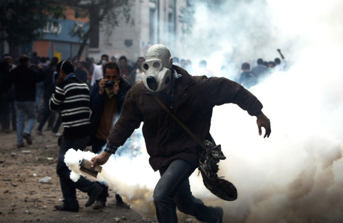 kilele:  A masked protester throws a gas canister towards Egyptian riot police, not seen, near the interior ministry during clashes in downtown Cairo, Egypt, on November 20, 2011. Photo by AP Photo/Tara Todras-Whitehill via In Focus