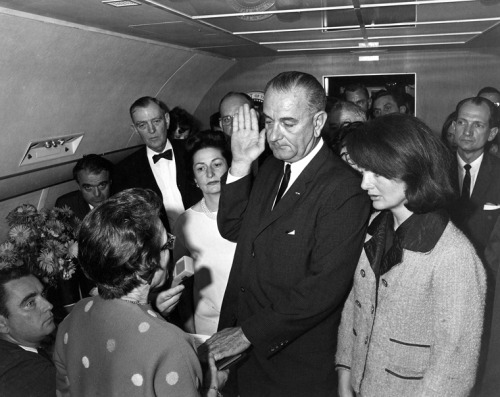 Lyndon B. Johnson takes the Presidential Oath of Office, November 22 1963 At 2:38 p.m. Lyndon B. Johnson stood in the tight, crowded compartment of Air Force One and took the oath of office.  U.S. District Court Judge Sarah Hughes administered the ceremony moments before take-off from Love Field in Dallas, Texas.  Lady Bird Johnson and Jacqueline Kennedy both stood next to the new president.