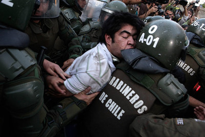fotojournalismus:  Santiago, Chile.  Police officers detain a human rights activist during demonstrations. [Credit : Luis Hidalgo/AP]