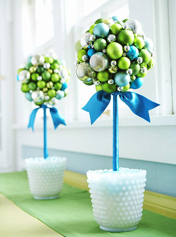 Christmas bauble topiary trees : Baubles cover foam balls supported by ribbon-wrapped dowels.  Milk-glass vases for vintage charm.