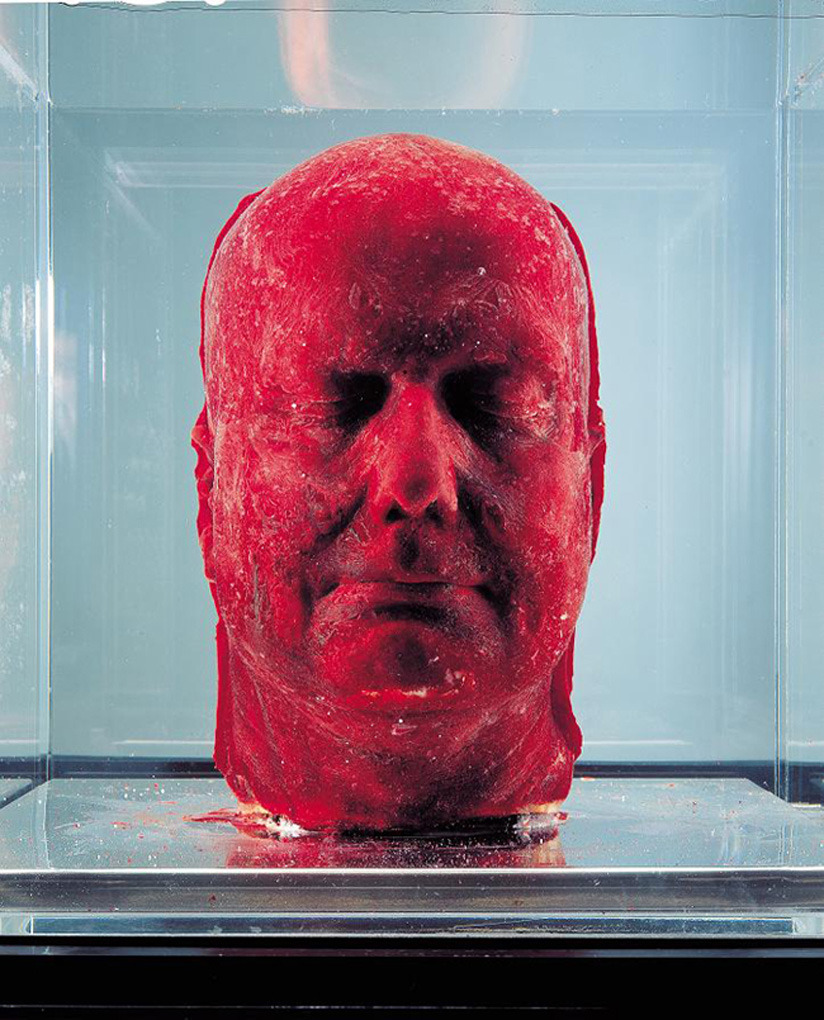 dissolvingss:  This is Marc Quinn's most famous piece of work, Self, made using 4.5 litres of his own blood, which was slowly extracted from his body over a period of five months and frozen in a cast of his face. Quinn has been making these roughly every five years since 1991, and each one must be maintained carefully in fridges. The fragility of the media means exhibiting is difficult - the head has to be placed into a glass case which is chilled from underneath. It reminds the audience of the fragility of existence and the precise conditions necessary for the flourishing of life