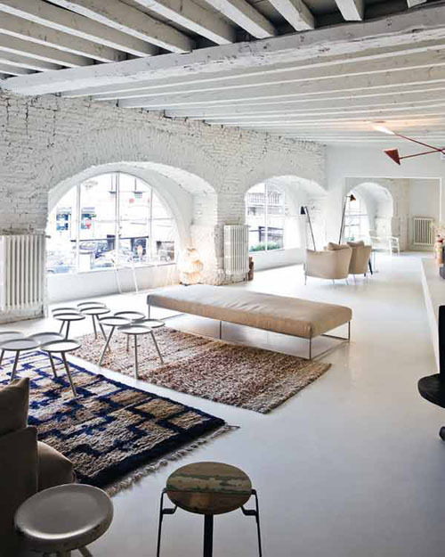 A gorgeous Italian loft with whitewashed brick walls and beamed ceilings gets a shot of subtle color from scattered area rugs (via Aubrey Road: whitewashed)