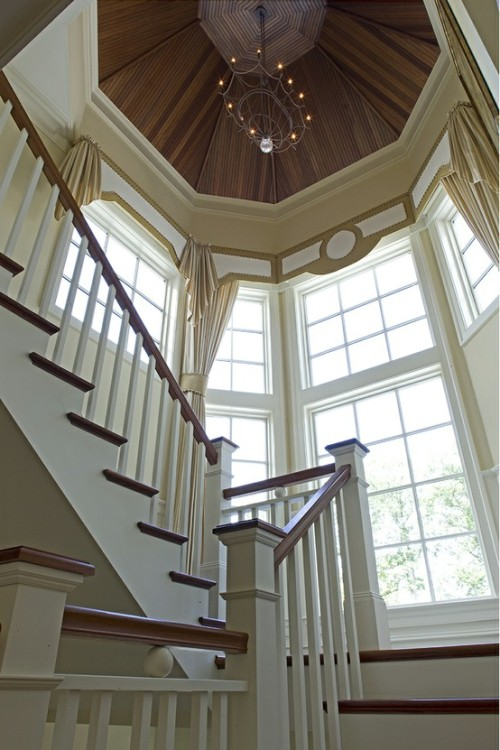 This staircase, of cherry wood and white, gains magnificence from a landing surrounded by a semi-circular wall of tall windows, and a high, high up peaked wooden tower ceiling. (via Stairways)