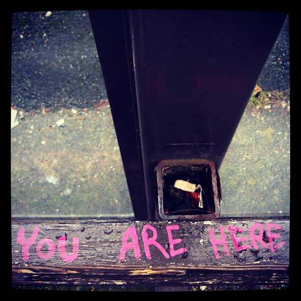 YOU ARE HERE #present #zen #mindful #aware #buddhist #here #now #random #interesting #insight #bench #graffiti #pink #typography #lettering  (Taken with instagram)