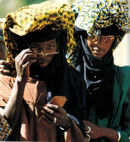 Shades & Swagger # 7 | Checking things out. Two young Fulani men from Mali. Colorful cloths given to them by admiring females are piled on top of their turbans. The girls make sure that the patterns of the fabrics they give match the patterns of the dresses they will wear that evening. From Carol Beckwith & Angela Fisher's Faces of Africa