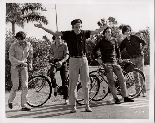 Ringo, John and George stand by their bikes. Paul shuffles cutely. Richard Lester directs.