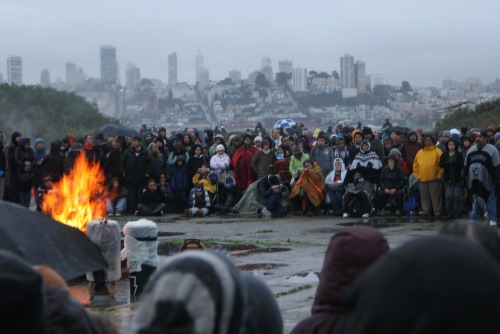 At the Indigenous People's Sunrise Gathering on Alcatraz. The tradition was born out of the occupation in the 1960s (abridged here via Wikipedia) and particularly fascinating given the current Occupy Movement:  According to the IAT, the Treaty of Fort Laramie (1868) between the U.S. and the Sioux returned all retired, abandoned or out-of-use federal land to the Native people from whom it was acquired. Since Alcatraz penitentiary had been closed on March 21, 1963, and the island had been declared surplus federal property in 1964, a number of Red Power activists felt the island qualified for a reclamation.  On March 8, 1964, a small group of Sioux demonstrated by occupying the island for four hours… this demonstration was an extension of already prevalent Bay Area street theater used to raise awareness. The protesters were publicly offering the federal government the same amount for the land that the government had initially offered them; at 47 cents per acre, this amounted to $9.40 for the entire rocky island, or $6.54 for the twelve usable acres.