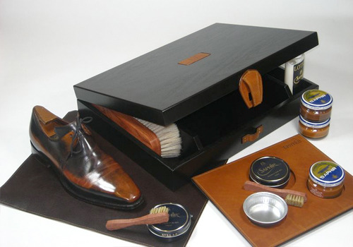 Q and Answer: How Should You Store Your Shoe Care Supplies? Matt writes to ask: Can you suggest a kit or supply chest for shoe care products? Ethan Desu once wrote something that I liked very much. He said that you should enjoy the process of polishing shoes, not just the results. Ethan learnt to polish shoes with a friend who liked to sit around, drink tea, and talk all afternoon. Polishing shoes was just a good excuse to do those things.  I find a lot of truth in that. I personally polish shoes alone, but I find the process very calming and meditative. Though you don't need a supply chest to enjoy the process, having something nice can make it feel more special. Let's review some options, going from the highest-end to the most affordable.  If money were no object, you can get a shoeshine kit from Ephtée (pictured above). Ephtée is a French company that specializes in handmade, customized shoe trunks and storage sets. Their supply chests cost anywhere from $600 to $1,500, depending on the box and what you get in it. A Suitable Wardrobe also has three incredibly handsome options that cost between $285 and $800. These are all very expensive, to be sure, but they're the nicest I've seen anywhere and they come as complete kits.  A bit more affordable, though still expensive, is Orvis' Gentleman's shoeshine kit. It's made by Col. Littleton, a Tennessee manufacturer of upscale leather goods. I find the finishing details on the box to be very nice. Saphir also makes a great kit. Both of these cost about $200 and I think they would make for fine gifts this Christmas.   There are many options below $200 as well. Famaco has some leather carriers in large and small sizes. The smaller one may be especially good if you travel often. There are also a number of traditional wooden boxes that can be had for under $50. Bexley has one in a natural color, and Shoe Shine Kit, Shoe Care Supplies, and Shoe Tree Marketplace have some with various finishes and engraving options. For even more affordable buys, do a search on eBay for shoe shine box, shoe shine kit, and shoe shine stand. You can also browse Etsy for the same terms. There are literally hundreds of options on those sites, many of which cost about $25 or so.  Finally, though it's nice to have a fancy box specially designed for shoe supplies, don't forget you can use almost any container. Jesse recently won this auction for a vintage sport-and-field shell carrier. It was made by Abercrombie and Fitch back when they were a fantastic, upscale sporting goods store and not disturbingly bad, teen apparel merchandiser. The carrier was originally meant to hold shotgun shells, but I think it would be perfect for shoe care supplies. If you live near good flea markets, you can probably find something just as great for not too painful of a price.