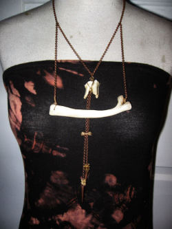 This beautiful one of a kind neck adornment is constructed with calf rib cut and sanded with precision. Intricately wire wrapped to copper rolo chain ,centrally balanced with a bovine tooth  Accented with cascading chains threaded with squirrel atlas bone and vertebra. Wire wrapped to 28 inch copper chain with lobster clasp. Teeth  were worn as a symbols of status and prowess,and worn to symbolize the  magical alliances with the animals. Animals were thought to be more in  touch with the cosmos then humans, with their superior physical and  sensory abilities, they were believed to possess magical and spiritual  powers. All components found in Buffalo/Warsaw Ny 2009/2010 FOR SALE NOW! WWW.ADORNEDIMMORTAL.COM