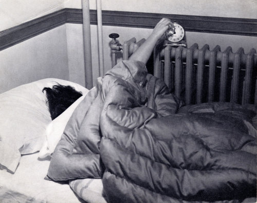 A sleepy student grabs for the alarm clock, c.1950s.  March, 2011 - Vassar Homepage Archive