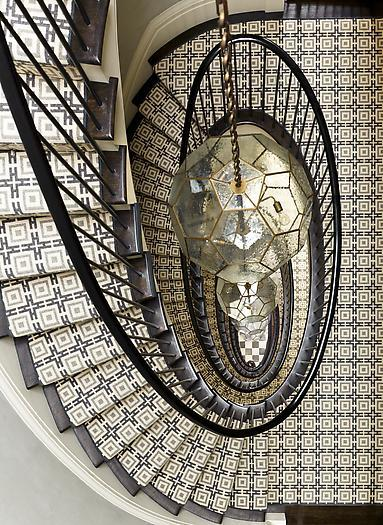 Amazing winding staircase covered with a geometric patterned carpet graces the entry of this New York City townhouse (via S.R. Gambrel - Portfolio)