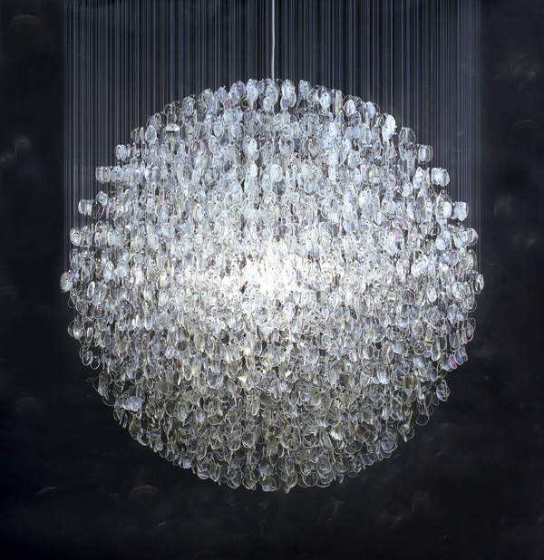 Optical (2007) by Stuart Haygarth.  The Optical chandelier is created from over 4500 prescription spectacle lenses. The lenses are hung on monofilament line which hang from a platform. The lenses form a spherical shape which imitates a disco mirror ball but rather than the light being reflected, the light is refracted through the many layers of glass lenses. A magical explosion of light is created. The light is illuminated by a clear 100w incandescent bulb.