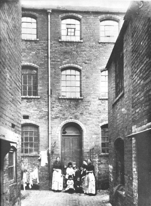 Slum, Birmingham, c. 1872 Broken windows, ragged clothes and narrow alleys. A typical Victorian slum. What I find touching about photographs of people in slums from the nineteenth century is that this picture is probably the only image that exists of these people. They would never have the means to purchase their own camera, and so street photography like this is the only way these people are able to live on in history. But for this picture, they would be completely forgotten. Who knows if the people here ever even saw this photograph of themselves? Its likely that they didn't.