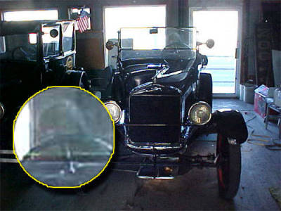 "Ghost Driver  ""On November 15, 2011, around 3:30 p.m, I took this photo of this Model T parked in storage for the Eklund Hotel in our town, Clayton, New Mexico,"" says Coby. ""There have always been stories about a ghost named Irene in the motel. It was built in the late 1800s. I felt/saw nothing unusual at the time I took the picture. It was simply needed for insurance coverage. Please check out the image behind the wheel and let me know what you think. Everyone I've shown this to thinks I need to do something about it!""  Coby, I am assuming that the picture was taken with a digital camera, which rules out a double exposure, so in my opinion the possibilities with this photo are these:  It is a hoaxed photo. The image is just a smudge on the glass that happens to look like a human head. It is a reflection of the photographer. It is a reflection of something else in the room. It is a ghost. I am leaning strongly toward the probability that this is a reflection of the photographer. It looks to be the right position and the right size, considering the distance of the photographer from the car. It even looks like there is something like a camera in front of the right eye. (See enlarged inset.)  This, of course, does not negate the possibility that the hotel is haunted, but I don't think this photo is evidence of that.  Coby comments further:  ""I took that picture, he says. I'm a 48-year-old male with a very, very short haircut and wear glasses. Does that impact your analysis?""  It does, Coby. The image does not look like it has short hair and does not appear to be wearing glasses. So perhaps that information lends more weight to this being a genuine ghost photo.  From: http://paranormal.about.com/od/ghostphotos/ig/Paranormal-Photo-Gallery/Ghost-Driver.htm?nl=1"