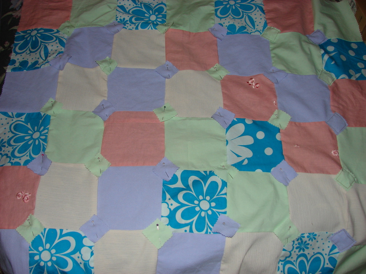 "This is a baby quilt I am making for my cousin. She's having a girl. Since our city has no fabric store anymore, I use old clothing for a lot of my material. Here I show from start .. to almost finish. I chose an old soft bed sheet for the back, then I stitched and X in the middle of each tiny diamond to ""quilt it to the back..now all I have to do is sew my binding strips around the edges and I'm finished.. yay me.!! BTW This is my first quilt EVER..  You can tell how my corners didn't add up to each other exactly.. I hid them with a little diamond in each ""intersection"" it really seems to hide a lot. Note* If you are a beginner like me, make sure you choose a busy pattern for your back fabric.. It helps hide any little imperfections. photo=nap"