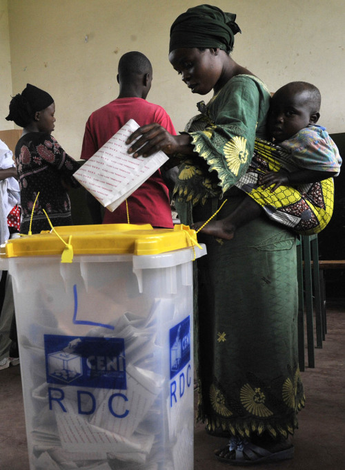 fotojournalismus:  A Congolese woman carrying her baby casts her vote in Goma during the presidential and legislative elections on November 28, 2011. The Democratic Republic of Congo held national elections Monday under a cloud of violence after clashes on the final day of campaigning left at least two people died. [Credit : Simon Maina/AFP/Getty]