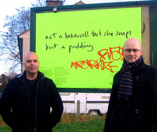 Paul Conneally and Gavin Wade by one of their street posters featuring a verse from the Three Estates Renga - 100 Verses for Three Estates. 'not a bakewell tart she snaps but a pudding'