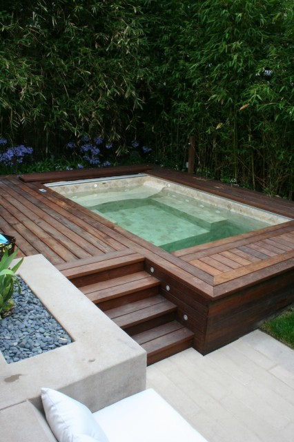 A true urban oasis… a hot tub nestles comfortably in a teakwood deck, flanked by a screen of bamboo, while a cushioned built-in stone seating area nearby provides further relaxation. (via contemporary - landscape - san francisco - by Frank & Grossman Landscape Contractors, Inc.)