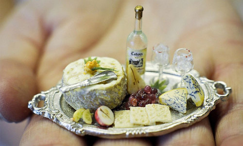 [image description: A dolls house sized cheese platter with miniature cheese, fruit, wine and biscuits]   OH MY FUCKING GOD TINY THINGS ARE THE BEST LOOK AT THIS SHIT THE LEVEL OF CRAFTSMANSHIP IN THIS INDIVIDUAL SEGMENTS IN THE LEMONS MOULD VEINS IN CHEESE SOMEONE PUT ALL THEIR TIME AND EFFORT INTO THIS BEAUTIFUL THING HUMANITY IS AWESOME.