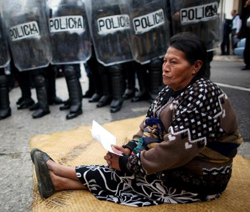 "moononwaters:  solodascavare:  A woman blocks the entrance to Congress as riot police stand guard in Guatemala City, Wednesday Nov. 23, 2011. Protesters are demanding that Congress approve the Ley de Vivienda, or Housing Act, which would allow them to attain legal titles to the lands where they built their homes. (Rodrigo Abd)  I like how her face is all ""No fucks given"""