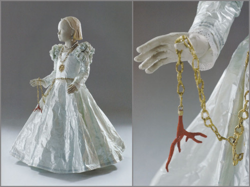 "Isabelle de Borchgrave – Bianca (""Bia"") de Medici, 2006 ""Based on another Bronzino portrait, the subject of this piece, Bia de Medici, was the illegitimate daughter of Florence's Duke Cosimo I de Medici. Bia was born prior to the Duke's first marriage, but died from a fever at the age of six. Cosimo commissioned Bronzino to paint the posthumous portrait, which remains one of his finest works. In the painting, and in the paper sculpture, Bia wears a medallion with her father's profile on it. Absent from the painting, however, is the coral amulet. de Borchgrave makes no mention of her inclusion of the coral, but it is reminiscent of several art historical themes. In ancient Rome, coral was seen as a symbol of fertility – but perhaps more relevant, is its use as a talisman or amulet.  A large number of 14th and 15th century paintings, depict children, and even the baby Jesus, wearing a coral talisman. Piero della Francesco's painting, Madonna di Senigallia best illustrates this."""