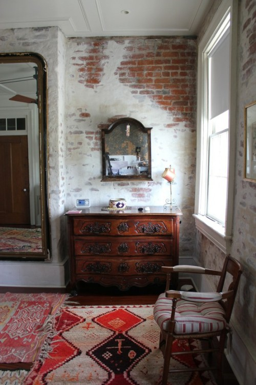 A bedroom full of history in this antebellum New Orleans home… above the antique dresser is a glass case filled with historic documents, photos and trinkets. Old rugs and exposed brick walls - partially painted - add to the comfortable, timeworn look. (via Stay: Race & Religious | Designtripper)