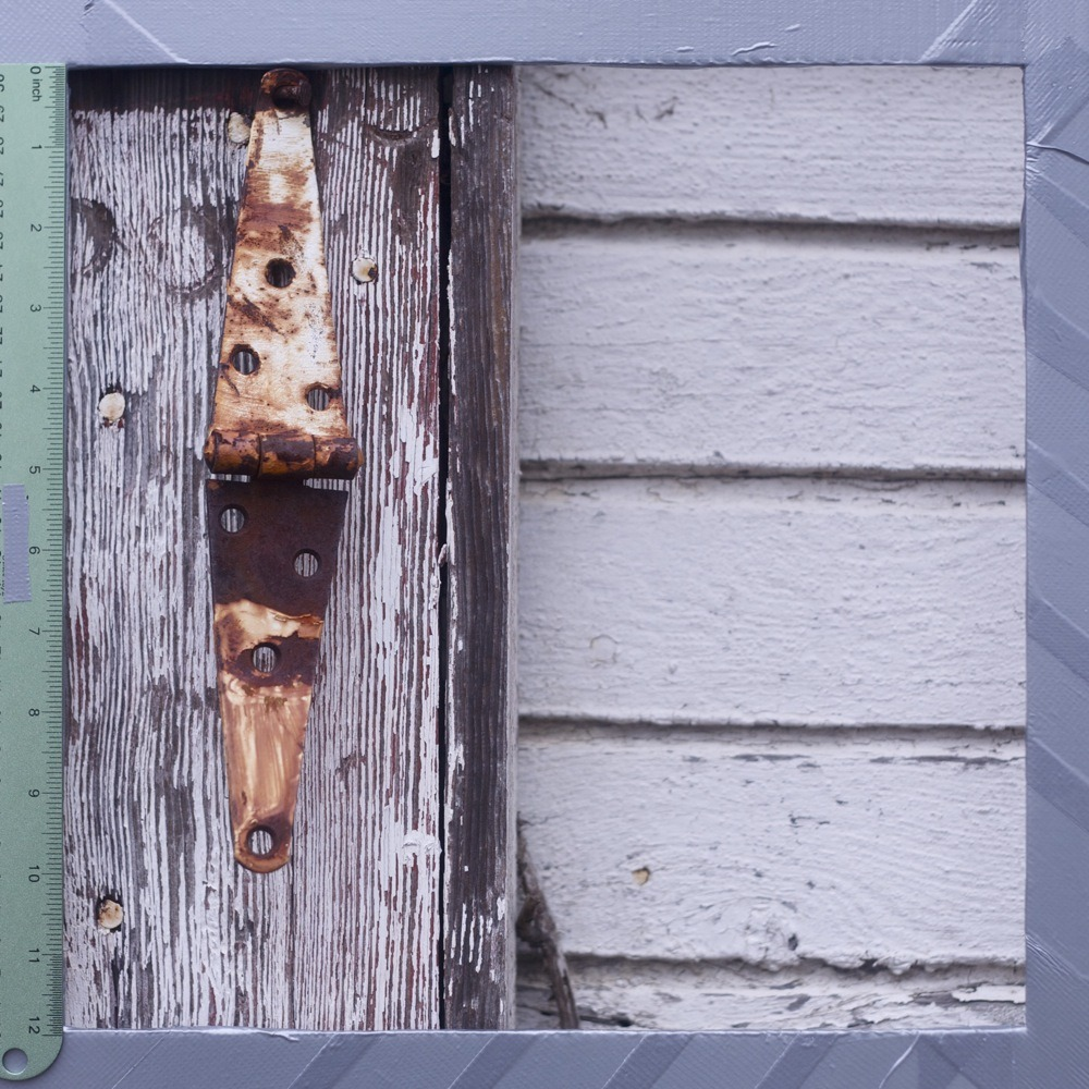Rusted metal hinge on weathered wood, peeling white paint, N Lombard/Lovely alley.