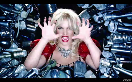 "32. Hold It Against Me The first video off Britney's seventh studio album is set on Earth, 2011. A giant flaming asteroid comes hurtling towards the planet, but instead of destroying the world, it brings some colourful lights. Oblivious to this - or perhaps super powered because of it - Britney is in a studio, getting reading for a photoshoot. Her perfume range makes yet another cameo, because obviously fragrance is important in a photoshoot. ""Hold It Against Me"" is crawling with product placement, including the dating site that also appeared in Lady Gaga's ""Telephone"" video. Every close-up of a strategically used product is a little bump in the flow of the video. It is a somewhat Gaga-inspired video, with both the costumes and the outrageous scenario. This could partly be due to the videos sharing director Jonas Akerlund, but yet all the elements of ""Hold It Against Me"" have been in previous Britney videos, just not in such a concentration. Trapped by her past, Britney is encircled by a wall of televisions, all playing her old music videos, while she wears a giant, multi-storey dress. What would sweet Britney of ""Sometimes"" say if she could see her future self? Suddenly Britney's freaky costume gets even freakier, with colourful paints spurting out of tubing at her fingertips. She jizzes the paint everywhere, giving the visions of past Britney a good soaking. While this is going on, an alternate Britney battles another Britney. The drama resolves itself, finishing with a good old fashioned formation dance with a nice big glitter bomb thrown in for good measure. A rainbow-coloured question mark appears on a staticy background. I don't know, Britney. You tell me."