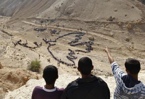 Palestinian students from United Nations schools in the Jericho area create an aerial image in the shape of Pablo PicassoŐs Peace Dove, at the foot of the Mount of Temptation just outside the West Bank city of Jericho, on November 25, 2011. The UN initiative was done in conjunction with the world-renowned aerial artist, John Quigley, to send out a peace message to the world. AFP PHOTO/ AHMAD GHARABL (via Pictures of the Week: November 28, 2011 | Plog — World, National Photos, Photography and Reportage — The Denver Post)