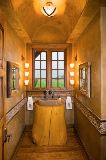 "Rustic nature… this powder room features an arched barrel ceiling and walls faux painted to have a ""leather"" look, rustic oak floors, an inlaid pebble stone chair rail, and a natural stone sink with a tree stump vanity. (via Bridger Canyon Residence - eclectic - powder room - other metros - by Locati Architects)"