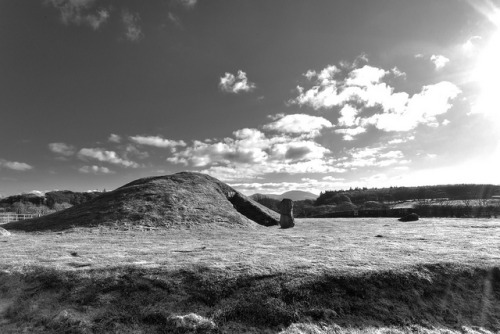 Bryn Celli Ddu - HDR - Black and White by Etrusia UK on Flickr.Via Flickr: Previous image of Bryn Celli Ddu converted to black and white. From Wikipedia: Bryn Celli Ddu is a prehistoric site on the Welsh island of Anglesey located near Llanddaniel Fab. Its name means 'the mound in the dark grove'. It was plundered in 1699 and archaeologically excavated between 1928 and 1929. During the Neolithic period a stone circle and henge stood at the site. An area of burnt material containing a small human bone from the ear, covered with a flat stone, was recovered. The stones were removed in the early Bronze Age when an archetypal passage grave was built over the top of the centre of the henge. A carved stone with a twisting, serpentine design stood in the burial chamber. It has since been moved to the National Museum of Wales and replaced with a replica standing outside. An earth barrow covering the grave is a twentieth century restoration; the original was probably much bigger. Norman Lockyer, who in 1906 published the first systematic study of megalithic astronomy, had argued that Bryn Celli Ddu marked the summer solstice. This was ridiculed at the time, but research by Christopher Knight and Robert Lomas in 1997- 98 showed this to be true. Knight and Lomas also claimed year round alignments allowed the site to be used as an agricultural calendar. Steve Burrow, curator of Neolithic archaeology at Amgueddfa Cymru (National Museum of Wales) has more recently supported the case for summer solstice alignment. This alignment links Bryn Celli Ddu to a handful of other sites, including Maes Howe and Newgrange, both of which point to the midwinter solstice. It has also been suggested that a feature similar to the 'lightbox' at Newgrange may be matched at Bryn Celli Ddu (Pitts, 2006). A row of five postholes previously thought to have been contemporary with the tomb (c.3000 BC) have recently been proven to be much earlier. Early results from a radiocarbon programme date pine charcoal from two of the pits to the Mesolithic (Pitts, 2006). ——— This is an HDR image made up from 7 exposures (-3 to +3) at f/32 processes in Photomatix.See where this picture was taken. [?]