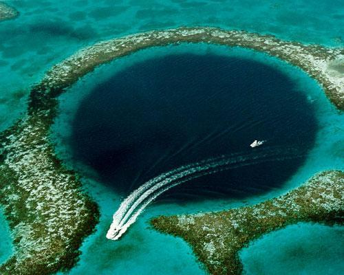 mothernaturenetwork:  The Great Blue Hole is a large underwater sinkhole off the coast of Belize that's more than 1,000 feet wide and 400 feet deep. It formed as a limestone cave system during the last ice age when sea levels were lower, and the caves flooded as the planet warmed and sea levels rose. Jacques-Yves Cousteau made the site famous in 1971 when he declared it one of the top 10 scuba diving sites in the world, and today it is a World Heritage Site.13 amazing sinkholes