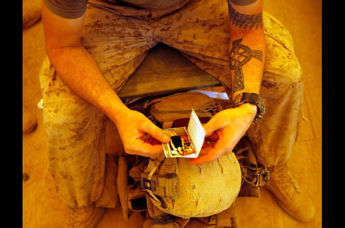 Lance Corporal Benjamin Buchanan from Jacksonville, North Carolina looks at a picture of his wife Cassandra before heading out.