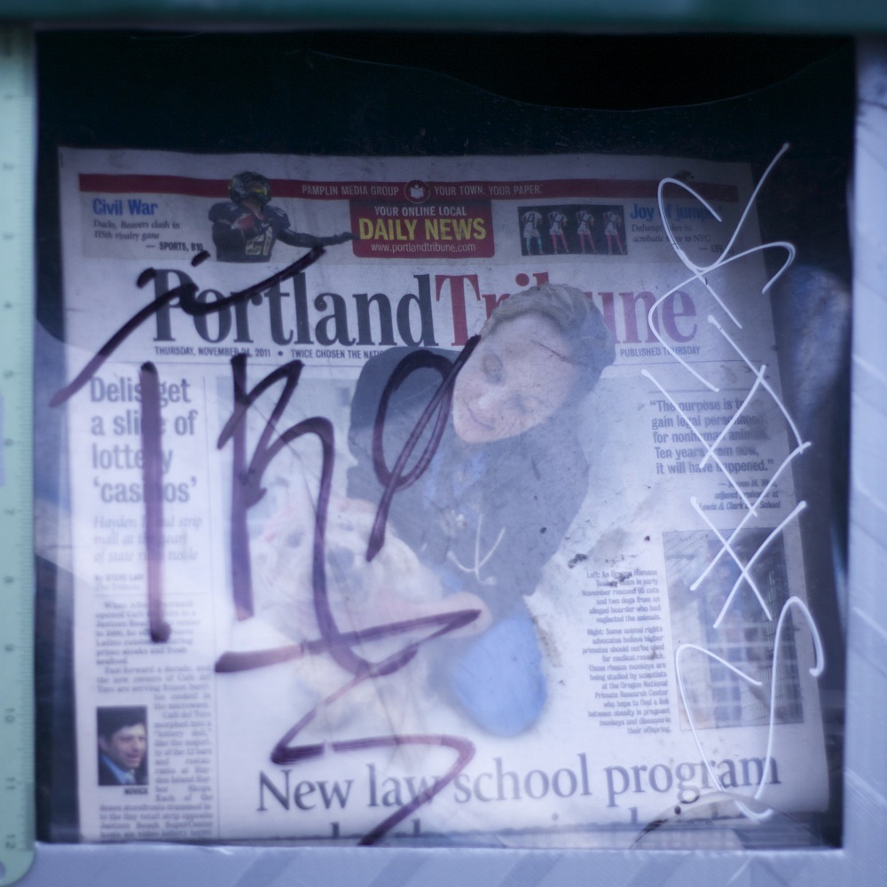 Portland Tribune dispenser with graffiti, N Lombard St.