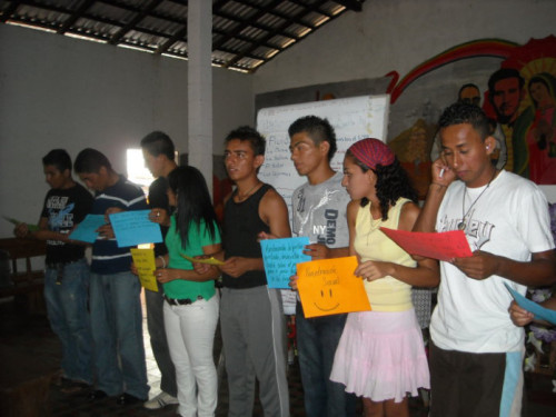 During a sex education lesson in El Salvador, the youth group members hold signs to organize themselves in the process of condom application. - Peace Corps Volunteer Jessica Rogala