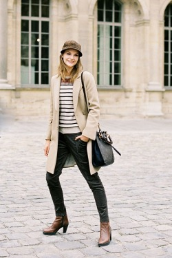 Camel coat over striped top and skinny pants with matching leather boots and topped with a brown cap.