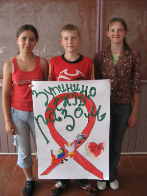 "I took this photo during an HIV/AIDS awareness camp held in Ukraine. The three students seen here, from the 8th form, created the poster as a project to show what they learned. The poster says ""We Stop AIDS Together"" in Ukrainian. - Peace Corps Education Volunteer Kathryn Trescott"
