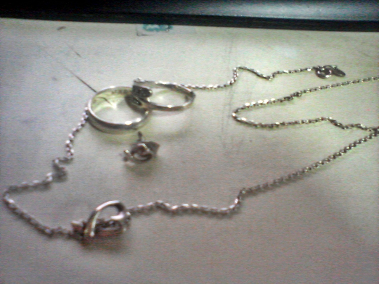 "My pieces of jewelry that I do not remove from my body— ever! That necklace is from Marty :) He gave that to me last July 16, 2010. I accidentally broke the original necklace of that heart pendant one day so he gave me a replacement without a pendant so I could use the same pendant he gave me :) The earring— yes, earring nalang, is from Marty too :) Match sa necklace, if you could notice na same ang form ng earring sa pendant. If you are asking why earring nalang siya kasi nawala ang pair niya last Thursday lang. :( I just notices when I touched my right ear na I was not wearing an earring there. I still wear that one until now— without its pair. Parang chuy lang. Haha! The two rings there stay at my right hand. The plain silver ring is a Christmas gift from Marty. Actually it has a ""MARTY"" engraved on on the inner portion of the ring. We had match rings. His has a ""FHOEBE"" on the inner portion too. Sadly, he lost his ring one time when he forgot where he put it in the gym. :