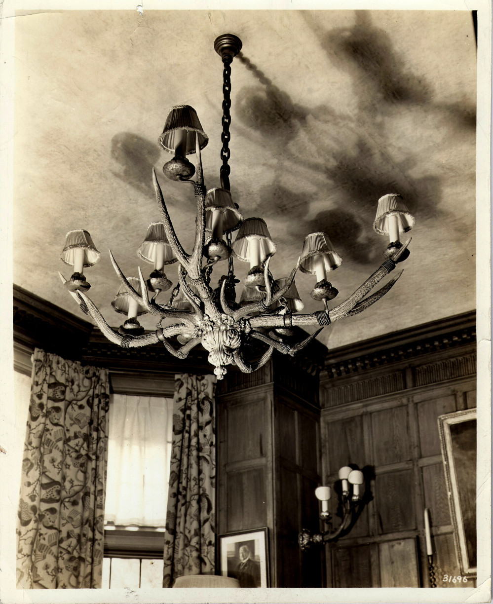 Antler chandelier and wall sconce on view in the Captain Frederick Pabst Mansion, Milwaukee.  Antlers often become trophies for deer hunters. In this case, deer antlers mounted with electric candles provide illumination and a rustic decorative touch to this interior. via: Cyril Colnik Archive, Villa Terrace Decorative Arts Museum
