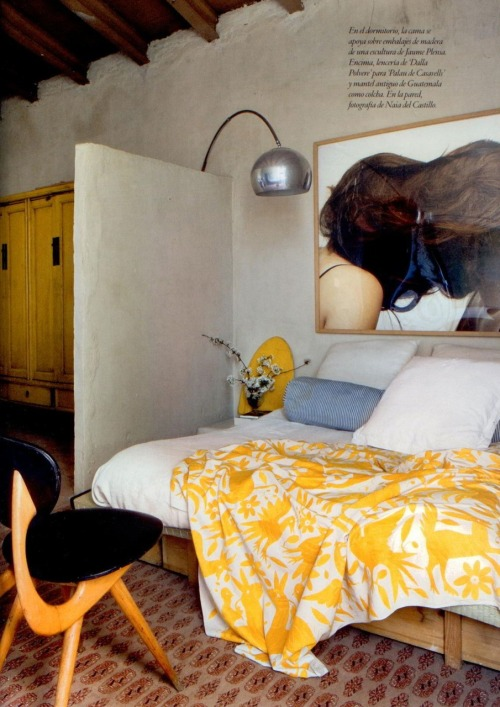 I love the vibrant use of yellow in this room. The spread is an antique Guatemalan cloth and the bed frame is made of wooden packaging. The contrast of this old building with the contemporary chair, lighting and photography creates such interest.