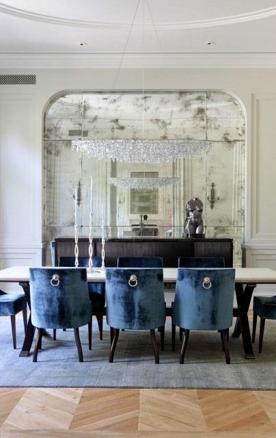 Contemporary furniture - blue velvet chairs, a crystal bowl chandelier - pairs nicely with a traditional dining room space, which features original wood herringbone floors, high moulded ceilings, and a wall inset with an old mirror. (via William Hefner Architecture Interiors & Landscape - traditional - dining room - los angeles - by Studio William Hefner)