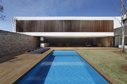 SN House, Londrina, Brazil | Studio Guilherme Torres  SN House displays an intriguing architecture, due to its original volumetry and large spans without any pillar support.  love this hallway  The house also features a solar heating system and rainwater capture.