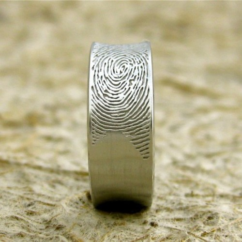 How sweet is this?  The bride or groom's finger print is engraved in the ring instead of their name or wedding date.  This way they will always have each other in their hands.