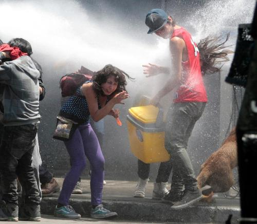 nickturse:  Protesters are hit with water from a police water canon during a march for       education reform in Santiago, Chile, Thursday Nov. 24, 2011. Protesters have       demanded more funding and other changes to the public education system. The       annual budget is due to be approved by Nov. 30. (Luis Hidalgo)