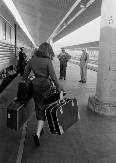 A woman disembarking a train, 1950s. Photo by Allan Grant.